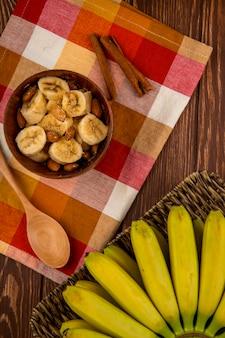 Vista superior de bananas fatiadas com amêndoa em uma tigela de madeira e cacho de bananas frescas em uma cesta de vime no rústico