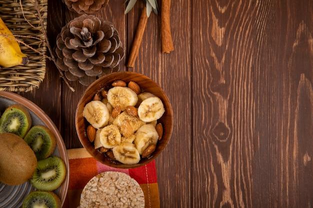 Vista superior de bananas fatiadas com amêndoa em uma tigela de madeira, fatias de kiwis em um prato e bolachas de arroz na rústica com espaço de cópia