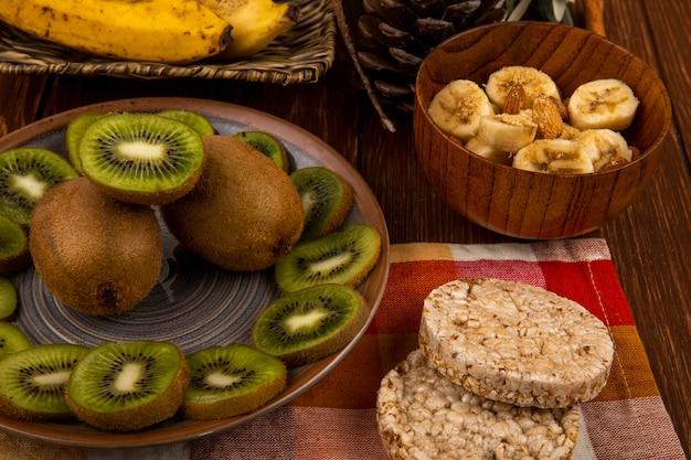 Vista superior de bananas fatiadas com amêndoa em uma tigela de madeira, fatias de kiwis em um prato e bolachas de arroz no rústico