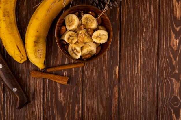 Vista superior de bananas fatiadas com amêndoa em uma tigela e bananas maduras frescas com paus de canela na madeira com espaço de cópia