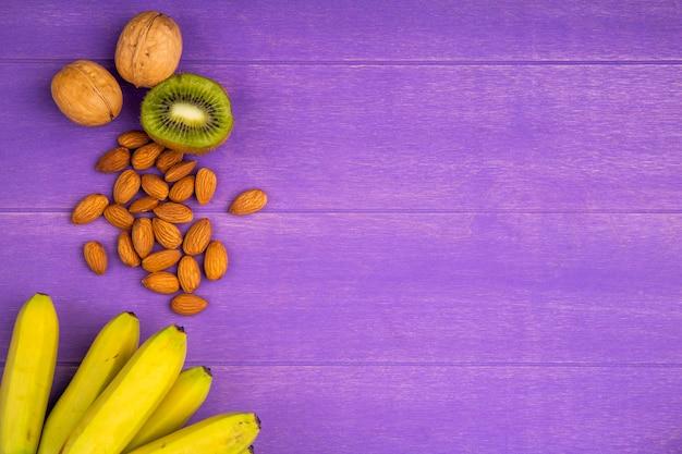 Vista superior de bananas maduras frescas com frutas de amêndoa e kiwi na madeira roxa com espaço de cópia
