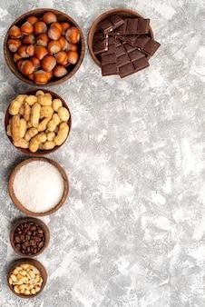 Vista superior de barras de chocolate com avelãs e amendoim na superfície branca