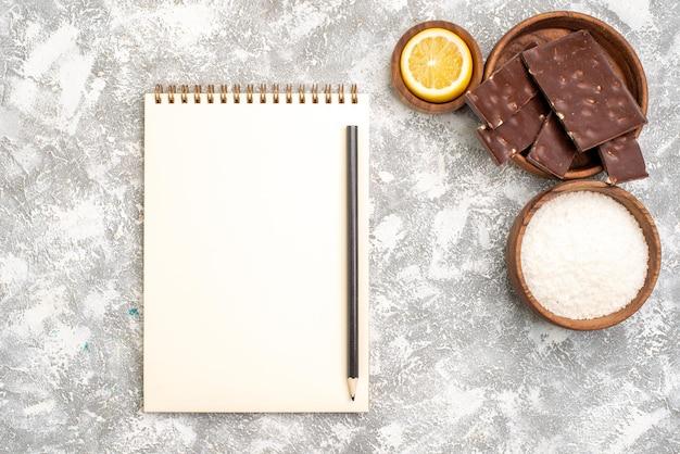 Vista superior de barras de chocolate deliciosas com rodelas de limão na superfície branca