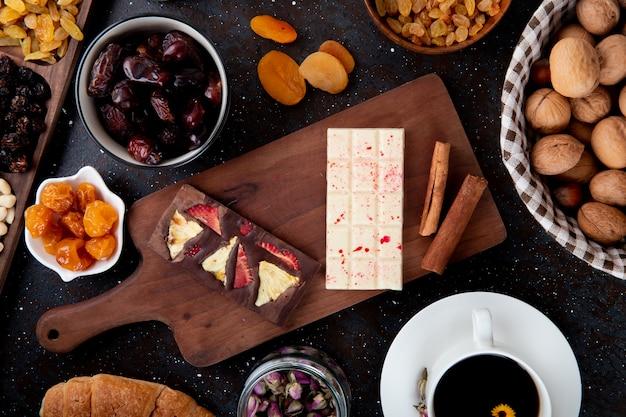 Vista superior de barras de chocolate escuras e brancas com frutas secas em uma placa de madeira, paus de canela, nozes e uma xícara de chá no rústico