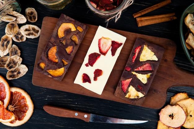 Vista superior de barras de chocolate escuras e brancas em uma tábua de madeira com várias frutas fatiadas secas em fundo preto