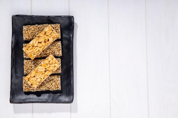 Vista superior de barras de mel com amendoim e sementes de girassol em uma bandeja preta com espaço de cópia no rústico
