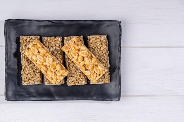 Vista superior de barras de mel com amendoim e sementes de girassol em uma bandeja preta no branco