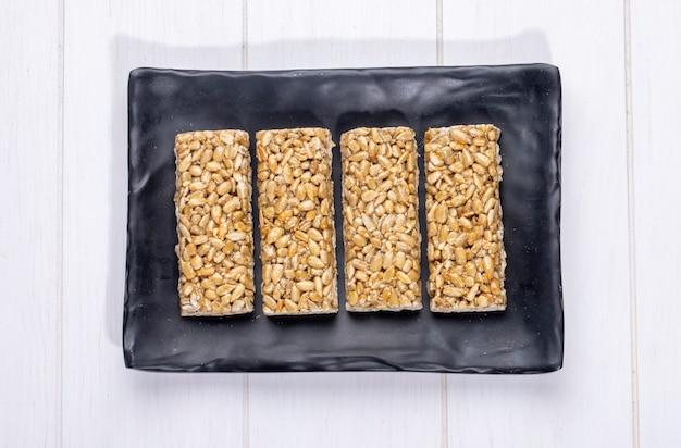 Vista superior de barras de mel com sementes de girassol em uma bandeja preta no rústico