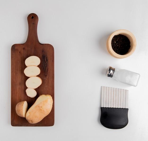 Vista superior de batata cortada e fatiada na tábua com sal pimenta preta e cortador de batatas fritas na superfície branca