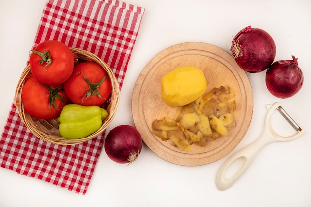 Vista superior de batata descascada fresca em uma placa de cozinha de madeira com descascador de tomates e pimenta em um balde em um pano xadrez com cebolas vermelhas isoladas em uma parede branca