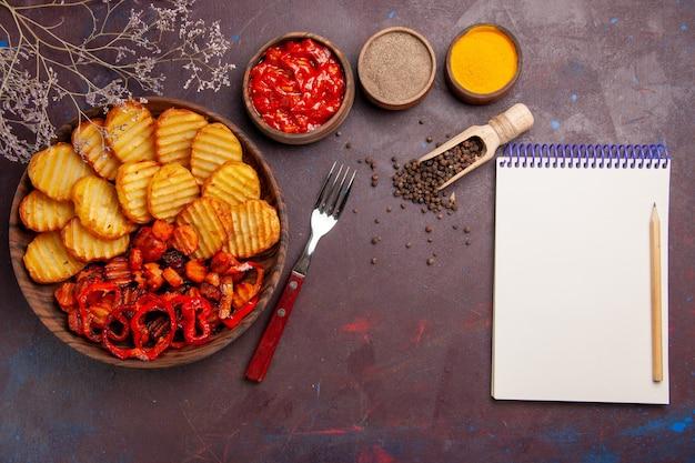 Vista superior de batatas assadas com legumes cozidos e temperos em espaço escuro