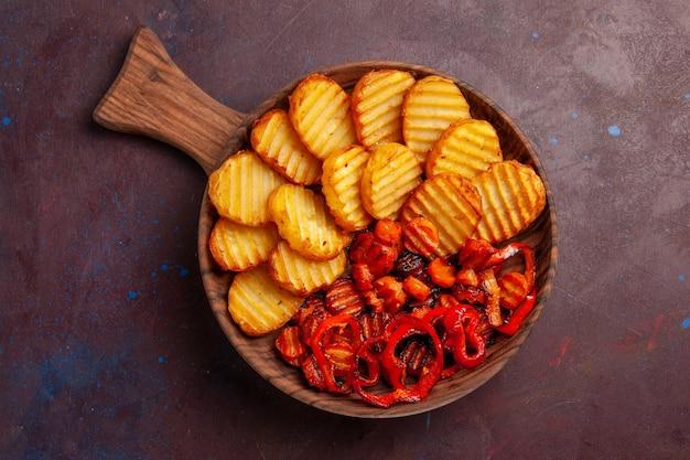Vista superior de batatas assadas com vegetais cozidos dentro do prato no espaço escuro