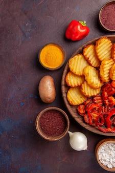 Vista superior de batatas assadas com vegetais cozidos em espaço escuro