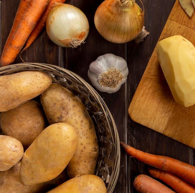Vista superior de batatas com alho e cebola