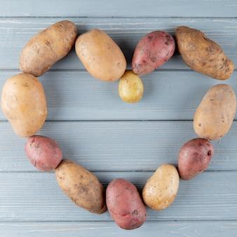 Vista superior de batatas em forma de coração com fundo de madeira com espaço de cópia