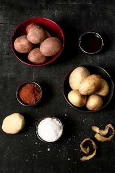 Vista superior de batatas em tigelas com sal e especiarias