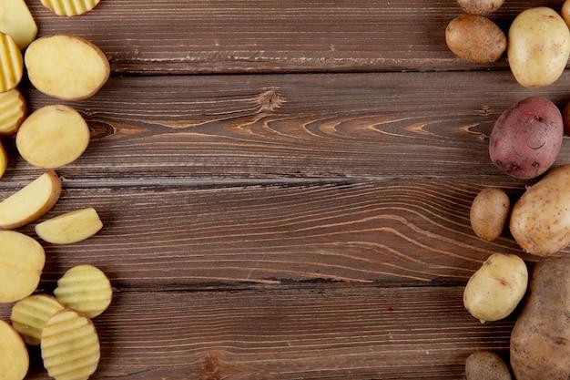 Vista superior de batatas fatiadas e inteiras nos lados esquerdo e direito e fundo de madeira com espaço de cópia