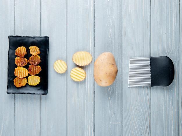 Vista superior de batatas fritas com batatas fatiadas e inteiras e cortador em fundo de madeira com espaço de cópia