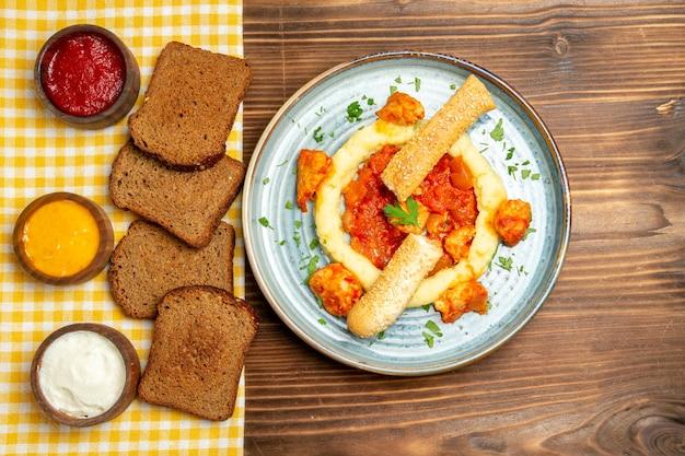 Vista superior de batatas fritas com fatias de frango ao molho e pão na refeição de prato de batata de mesa marrom