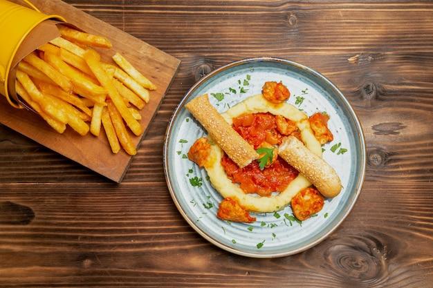 Vista superior de batatas fritas com fatias de frango na mesa marrom
