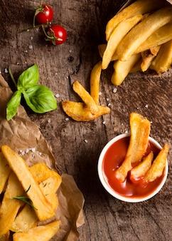 Vista superior de batatas fritas com ketchup e ervas