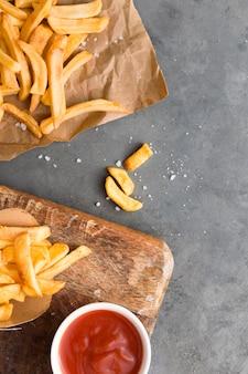 Vista superior de batatas fritas com ketchup e sal