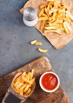 Vista superior de batatas fritas com ketchup e saleiro