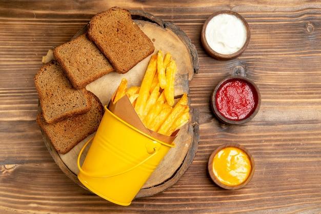 Vista superior de batatas fritas com pão preto e temperos na mesa marrom