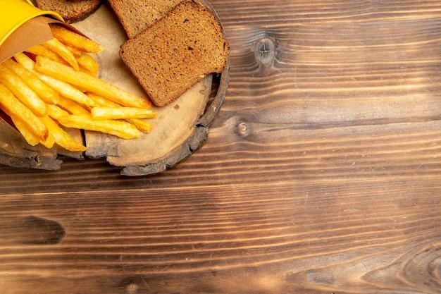 Vista superior de batatas fritas com pão preto na mesa marrom