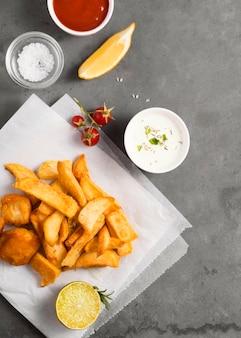 Vista superior de batatas fritas com tigela de molho e ketchup