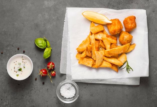 Vista superior de batatas fritas com tigela de molho e tomate