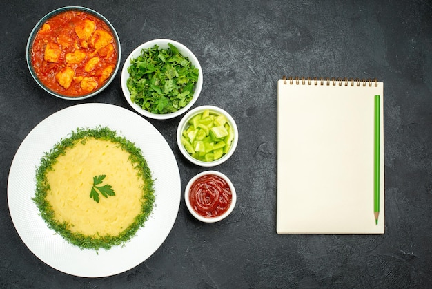 Vista superior de batatas fritas com verduras e molho de tomate na cinza