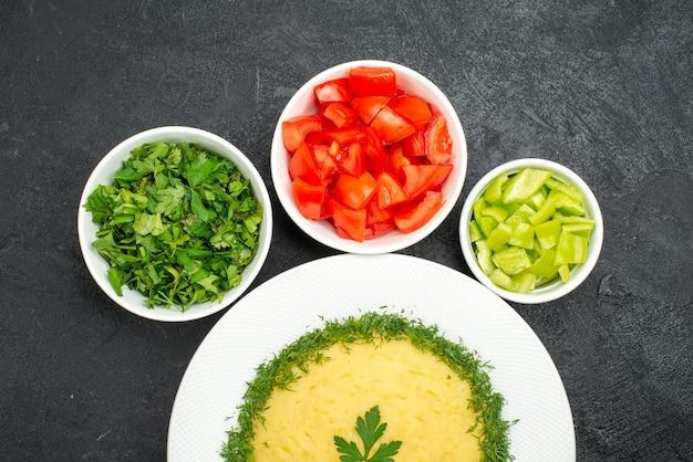 Vista superior de batatas fritas com verduras e tomates fatiados em cinza
