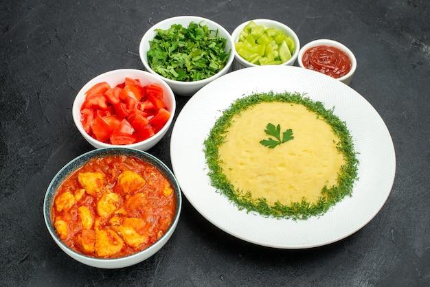 Vista superior de batatas fritas com verduras e tomates fatiados na mesa cinza