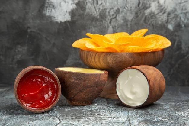 Vista superior de batatas fritas crocantes decoradas com maionese em forma de flor e ketchup na mesa cinza