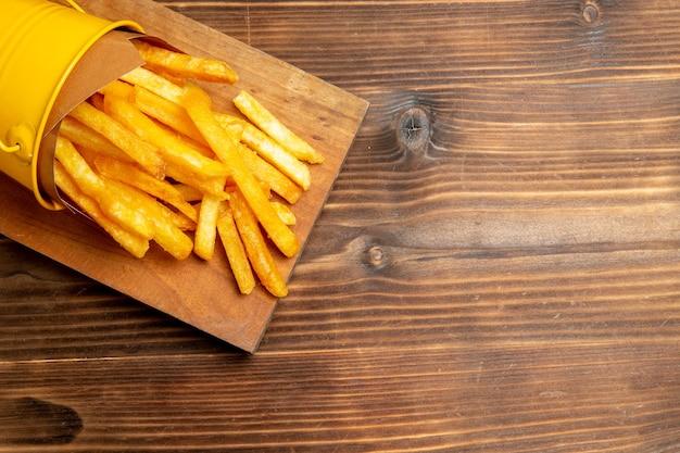 Vista superior de batatas fritas dentro de uma pequena cesta na mesa marrom