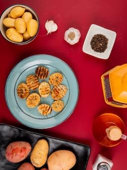 Vista superior de batatas fritas e não cozidas em pratos e tigela com ralador de alho manteiga pimenta na mesa de bordo