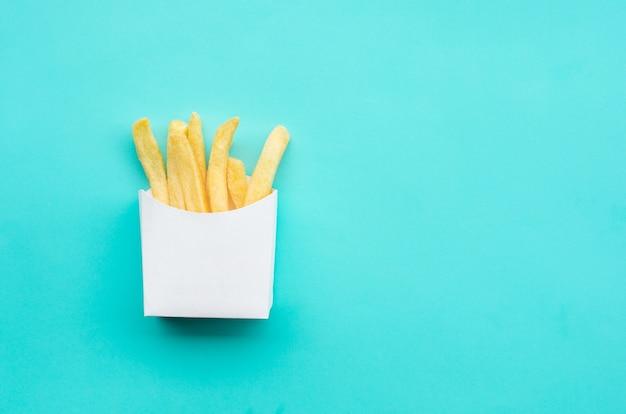 Vista superior de batatas fritas em fundo azul