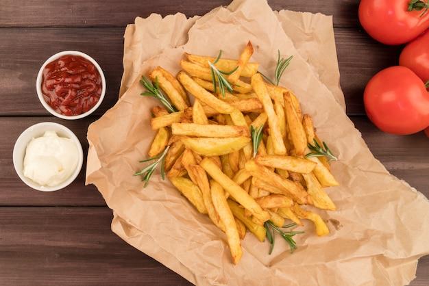 Vista superior de batatas fritas em saco de papelão com ketchup