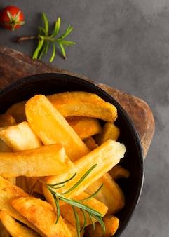 Vista superior de batatas fritas em uma tigela com ervas