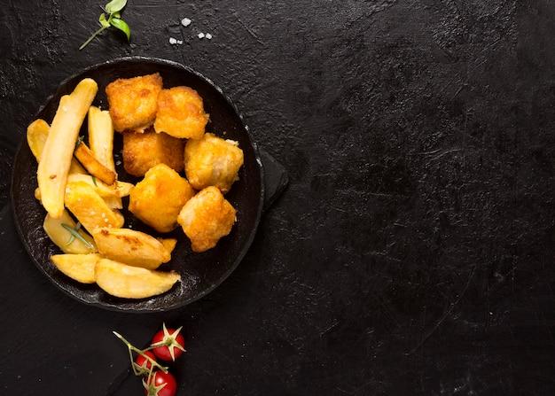 Vista superior de batatas fritas em uma tigela com espaço de cópia e sal