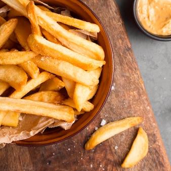 Vista superior de batatas fritas em uma tigela com sal