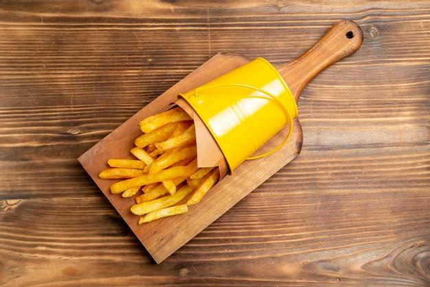 Vista superior de batatas fritas na mesa marrom