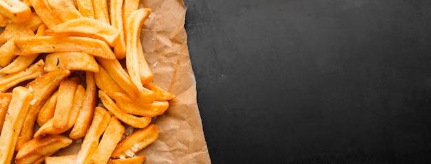 Vista superior de batatas fritas no papel com espaço de cópia