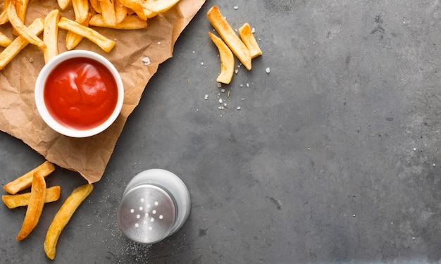 Vista superior de batatas fritas no papel com sal e ketchup