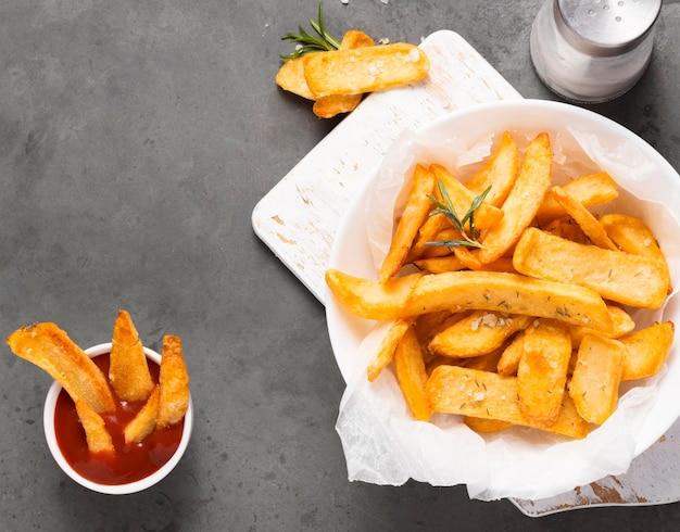 Vista superior de batatas fritas no prato com ketchup e saleiro