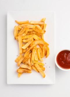 Vista superior de batatas fritas no prato com molho de ketchup