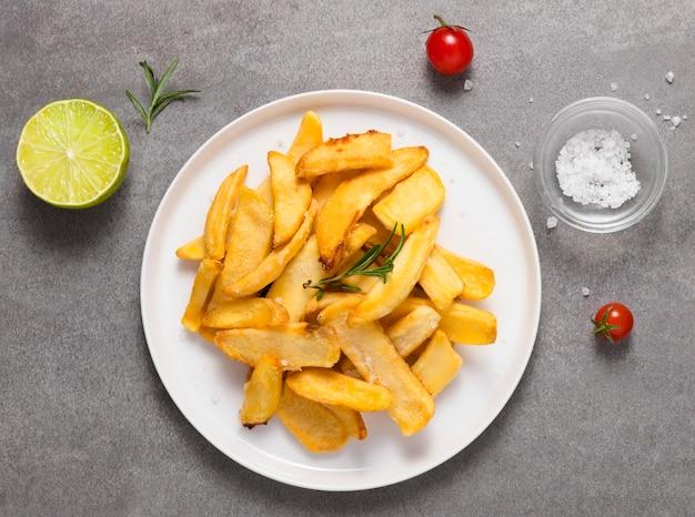 Vista superior de batatas fritas no prato com sal e tomate
