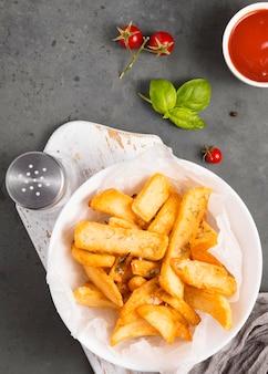 Vista superior de batatas fritas no prato com saleiro e ketchup