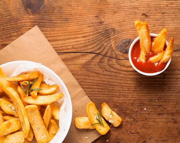 Vista superior de batatas fritas no prato com tigela de ketchup